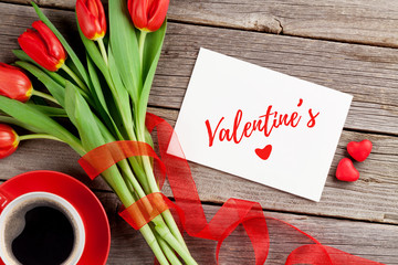 Red tulips, greeting card and candy hearts