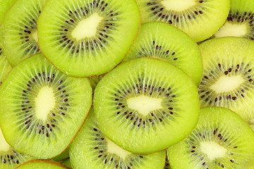 slices of fresh green kiwi fruits food background texture