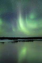 Aurora borealis over a lake in winter, Finnish Lapland