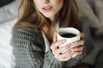 Unrecognizable woman with coffee mug on bed