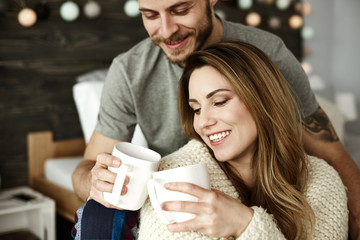 In love couple drinking coffee in bedroom
