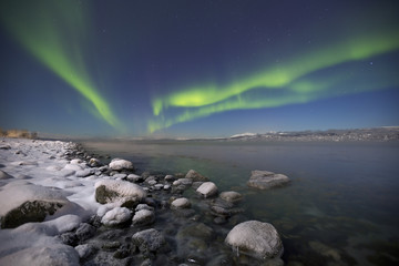 Aurora borealis over a moonlit fjord in northern Norway