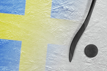 Image of a Swedish flag and a hockey stick with a puck