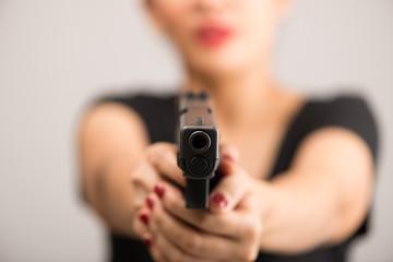 young woman asian girl holding a gun aiming at the gun, with selective focus