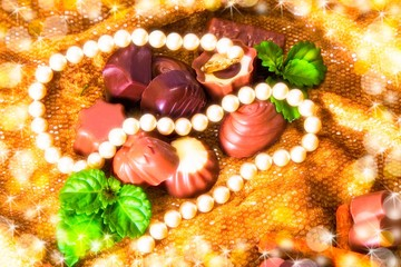assortment of chocolate pralines with pearl necklace