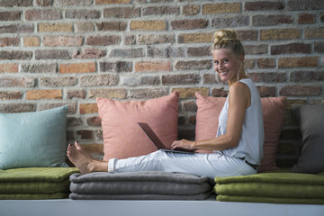Mature woman sitting on couch, usine laptop