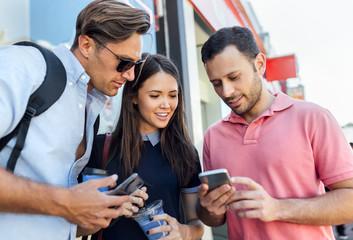 UK, London, Portobello Road, three  friends looking at cell phone