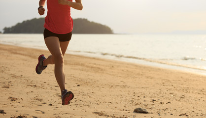 young fitness female runner running at beach