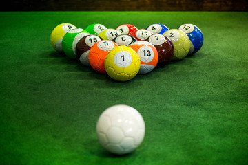 Shot of foot pool balls standing on green table. Foot Pool is the hybrid combination of pool and soccer. Big billiard balls