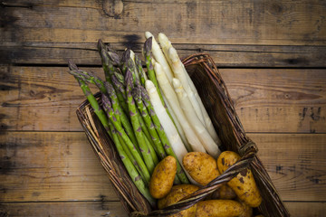 White and green asparagus and new potatoes in wickerbasket