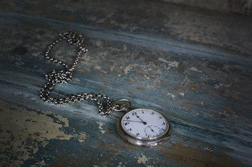 Old pocket watch showing five to twelve