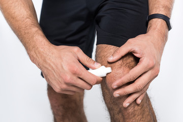 cropped shot of man applying ointment on knee