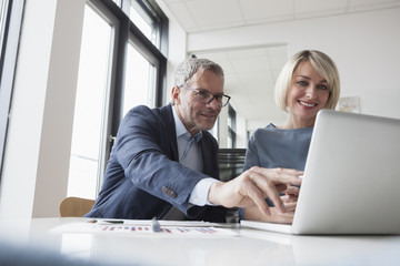 Businessman and woman working together in office using laptop