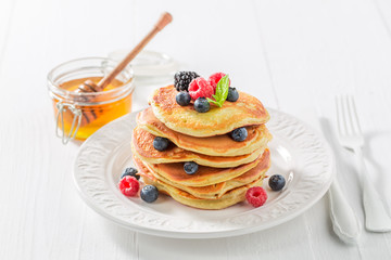 Sweet and tasty american pancakes with maple syrup and berries