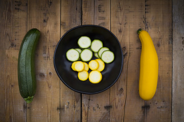 Yellow and green zucchini and bowl of zucchini slices on wood