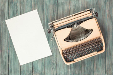 Retro old portable compact typewriter circa 70th and paper sheet blank on mint green grunge wooden desk. Vintage style filtered photo