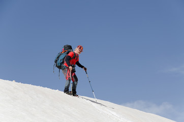 a middle aged mountaineer with his bag on his back descending from a snowy hill with the help of his hiking sticks.