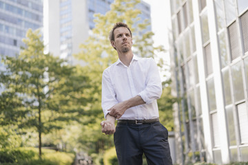 Portrait of confident businessman in the city rolling up his sleeves
