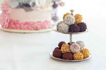Pyramid of chocolate balls. Chocolate candies covered with icing, nuts, coconut chips. Festive table settings. Light background