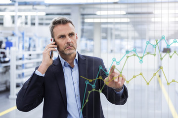 Businessman on cell phone looking at graph on glass pane in factory hall