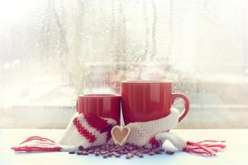 together with your favorite coffee drink/ small and large red mug in scarf is decorated with cookie in the shape of heart on background  window after rain spring