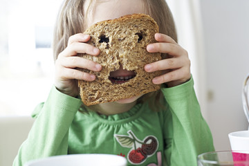 Little girl looking through holes in slice of bread