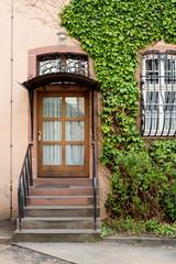 altes Haus mit Holztür und Gitter vor dem Fenster