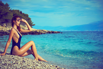 slim attractive woman posing in blue waters of Adriatic sea beach
