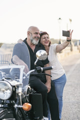 Senior couple taking selfie on sidecar bike. Jaen, Spain