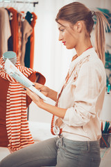 Young beautiful woman with tape measure draped over the neck, sit on a table beside dressed mannequin and looking at sketches of clothing.