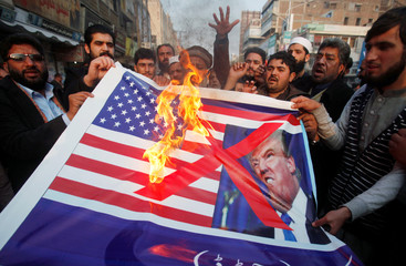 People burn a sign depicting a U.S. flag and a picture of U.S. President Trump as they take part in an anti-U.S. rally in Peshawar