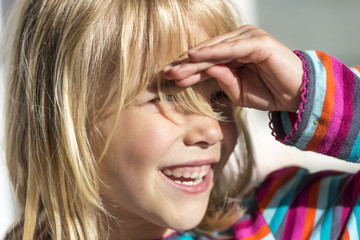 Portrait of little girl shielding her eyes while looking at distance
