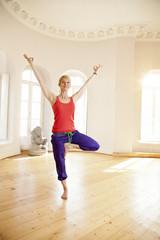 Happy woman in sunny yoga studio holding tree pose