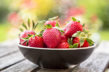 Bowl of strawberries on wooden garden table