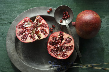 Two halves of pomegranate on tin plate