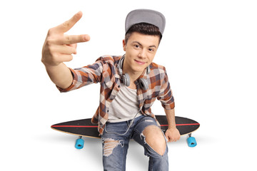 Teenage hipster sitting on a longboard and making a peace hand gesture