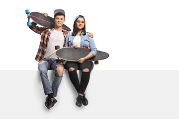 Teenagers with longboards sitting on a panel