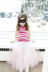 Portrait of little girl wearing mask sitting on window sill