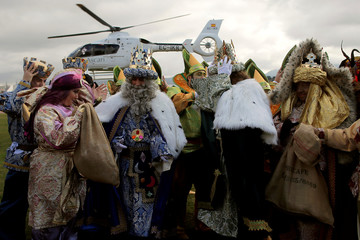 Men dressed up as the Three Wise Men and a woman in a Royal postman's costume protect themselves from the wind of a helicopter after arriving in it to take part in the traditional Epiphany parade in Ronda