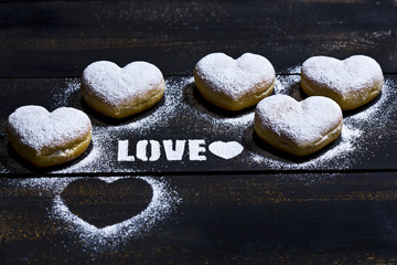 The word 'Love' stenciled with icing sugar and five heart-shaped crullers on dark wood
