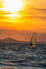 Sunset over the sea or ocean and extreme freestyle sport windsurfing, windsurfer in sea
