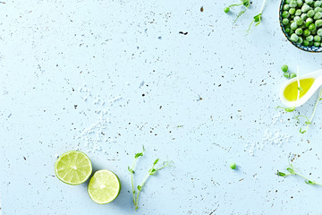 Symbolic food background with lime, olive oil, frozen peas and pea sprouts