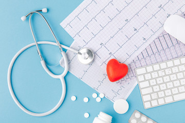 stethoscope, paper with cardiogram, scattered pills, red heart and keyboard isolated on blue background