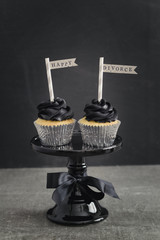 Two cup cakes with black coloured buttercream topping and pennons on a cake stand