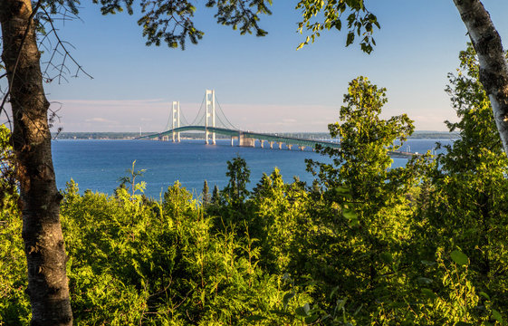 Summer Vacation At Mackinaw. View of the Mackinac Bridge framed by the lush green forest of the Upper Peninsula with the blue waters of Mackinaw at the horizon. St. Ignace, Michigan.