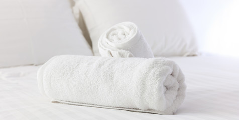 Hotel's bedroom. White fluffy, rolled towels, linen sheets and pillows on a bed. Close up view.