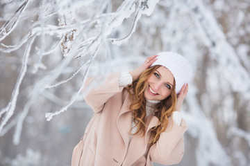 Portrait of smiling beautiful woman in a beige coat in a winter