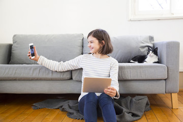 Happy girl with tablet sitting on the floor of the living room taking selfie with smartphone