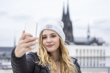 Germany, Cologne, portrait of smiling young woman taking selfie with smartphone