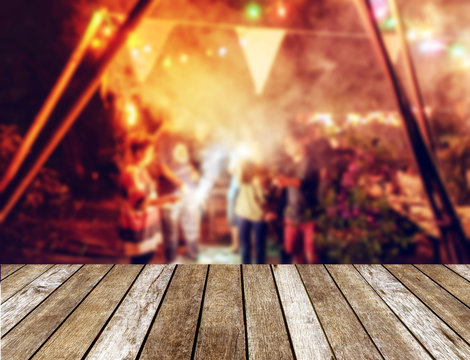 Wooden table top on blurred new year celebration friends party with light illumination